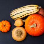 Organic Autumn food concept assortment vegetables Pumpkins, sweet potatoes, Delicata Squash, yellow turnip on black background